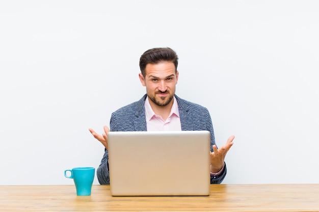 Jovem empresário bonitão se sentindo sem noção e confuso, sem ter certeza de qual opção ou opção escolher, imaginando