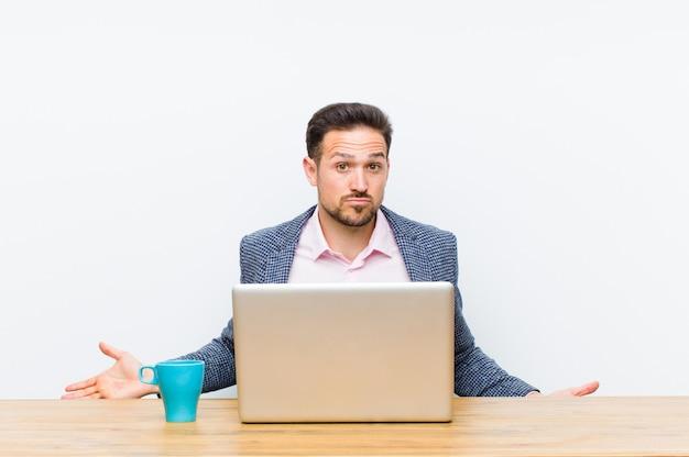 Jovem empresário bonitão se sentindo sem noção e confuso, sem ter ideia, absolutamente intrigado com um olhar tolo ou tolo