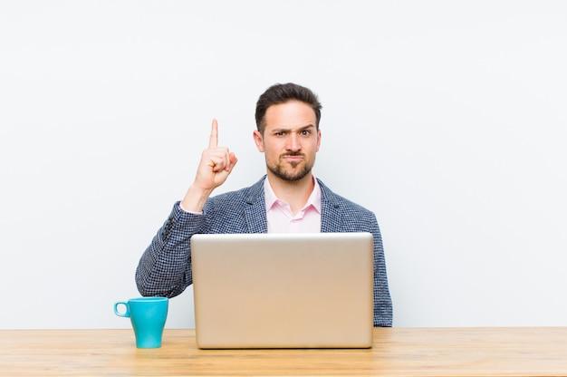 Jovem empresário bonitão se sentindo um gênio segurando o dedo orgulhosamente no ar depois de perceber uma ótima idéia, dizendo eureka