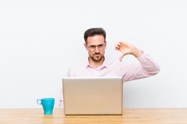 Jovem empresário bonitão, sentindo-se zangado, irritado, irritado, decepcionado ou descontente, mostrando os polegares para baixo com um olhar sério