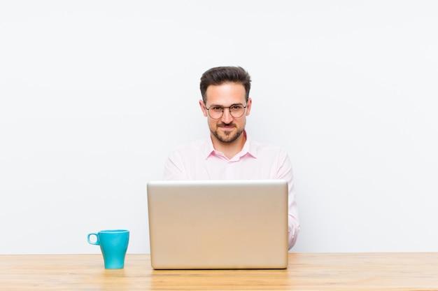Jovem empresário bonitão sorrindo alegremente com um olhar amigável, confiante e positivo, oferecendo e mostrando um objeto ou conceito