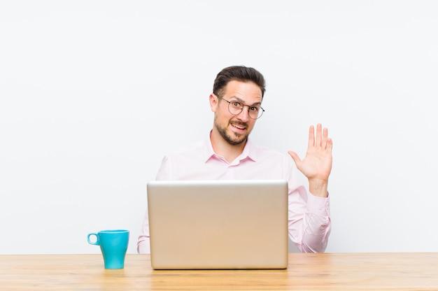 Jovem empresário bonitão sorrindo alegremente e alegremente, acenando com a mão, dando as boas-vindas e cumprimentando-o ou dizendo adeus