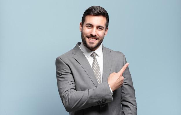 Jovem empresário bonitão sorrindo alegremente, sentindo-se feliz e apontando para os lados e para cima, mostrando o objeto no espaço da cópia
