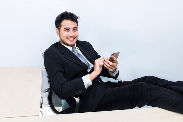 Jovem empresário bonitão sorrindo e falando com o telefone no escritório