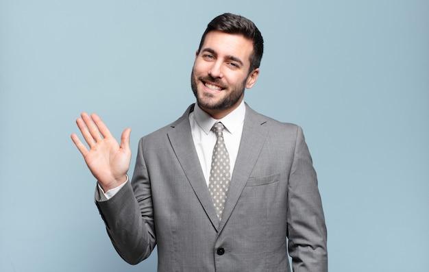 Jovem empresário bonitão sorrindo feliz e alegre, acenando com a mão, dando as boas-vindas e cumprimentando você ou dizendo adeus