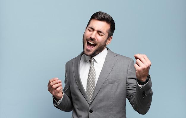 Jovem empresário bonitão sorrindo, sentindo-se despreocupado, relaxado e feliz, dançando e ouvindo música, se divertindo em uma festa