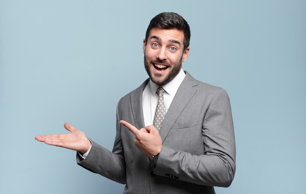 Jovem empresário bonitão sorrindo, sentindo-se feliz, despreocupado e satisfeito, apontando para um conceito ou ideia no espaço da cópia ao lado