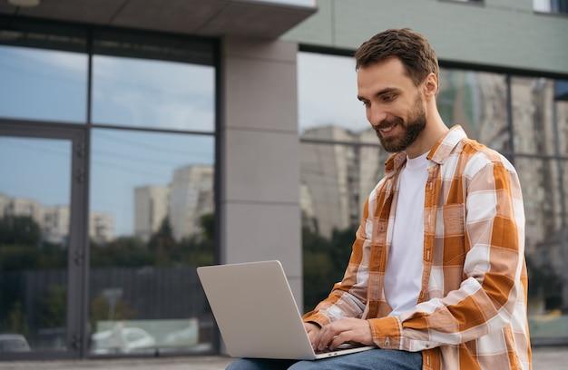 Jovem empresário bonitão usando laptop, digitando e trabalhando online