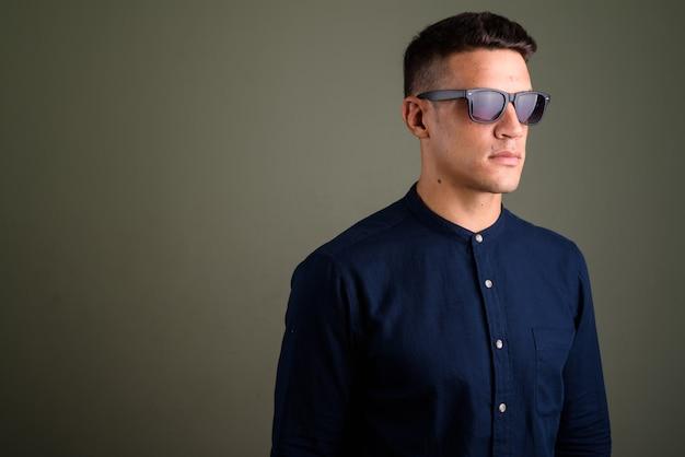 Jovem empresário bonitão usando óculos escuros contra ba colorido