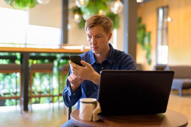 Jovem empresário bonitão usando telefone enquanto trabalhava em uma cafeteria