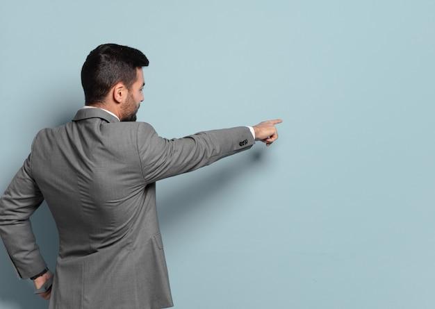 Jovem empresário bonito apontando ou mostrando um lugar vazio para o seu conceito