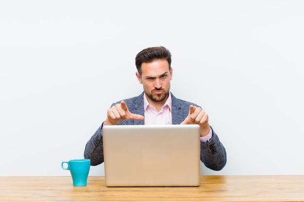 Jovem empresário bonito apontando para a frente na câmera com os dedos e expressão de raiva, dizendo para fazer o seu dever