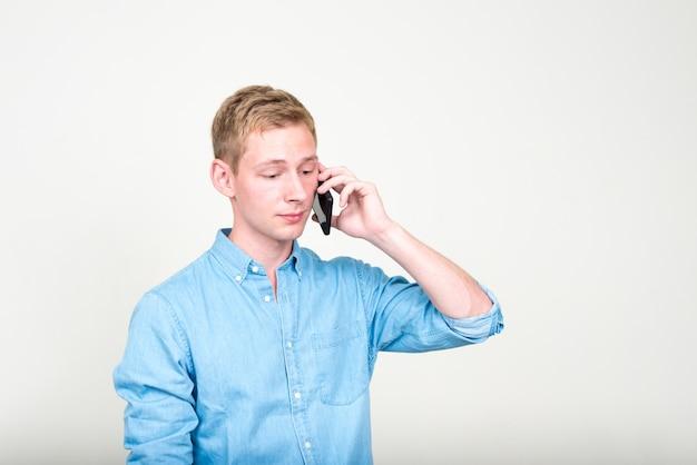 Jovem empresário bonito com cabelo loiro contra uma parede branca