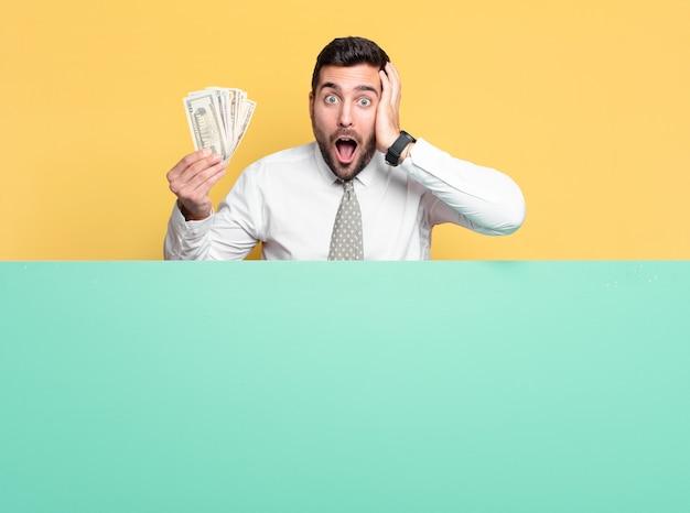 Jovem empresário bonito com notas de dólar. conceito de riqueza
