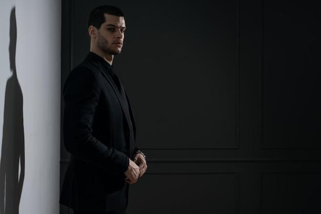 Jovem empresário bonito de camisa preta e terno preto