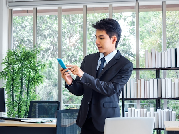 Jovem empresário bonito de terno e gravata em pé ao usar o celular azul perto da mesa com o computador laptop, estante de livros e janela de vidro no escritório com árvore verde natural.