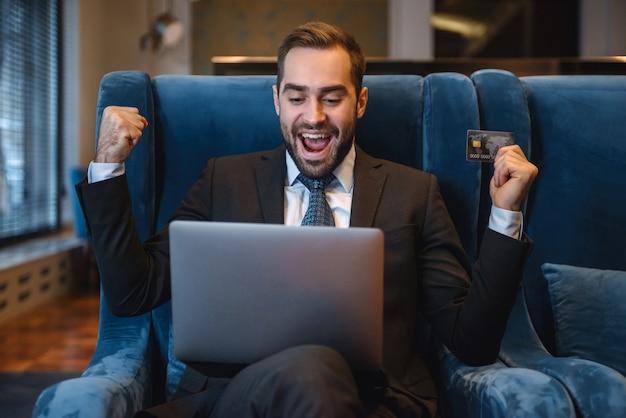 Jovem empresário bonito de terno sentado no saguão do hotel, usando um laptop e mostrando um cartão de crédito de plástico