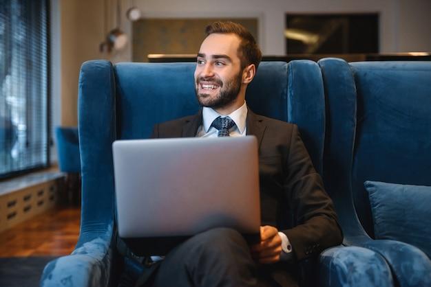 Jovem empresário bonito de terno sentado no saguão do hotel, usando um laptop