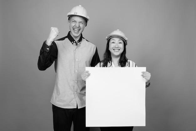 Jovem empresário bonito e mulher de negócios asiática madura usando capacete contra uma parede cinza