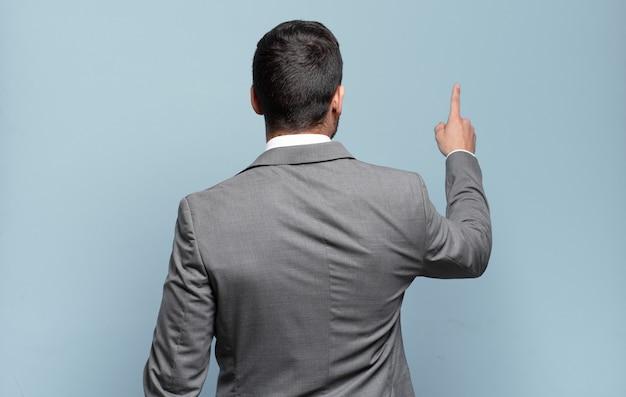 Jovem empresário bonito em pé e apontando para um objeto no espaço da cópia, vista traseira