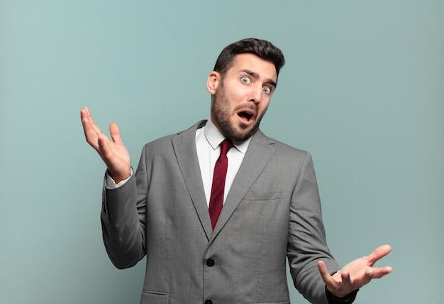 Jovem empresário bonito encolhendo os ombros com uma expressão estúpida, maluca, confusa e perplexa