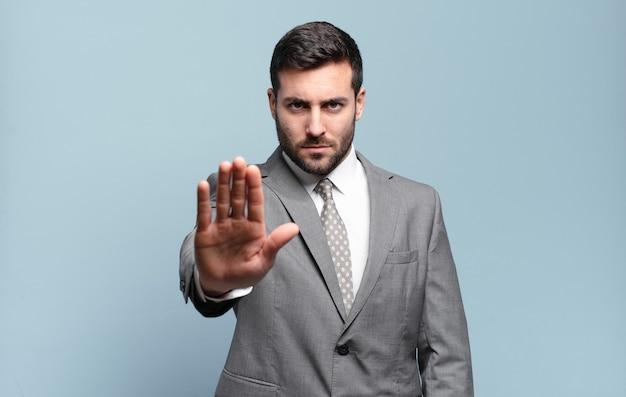 Jovem empresário bonito parecendo sério, severo, descontente e irritado mostrando a palma da mão aberta fazendo gesto de parada