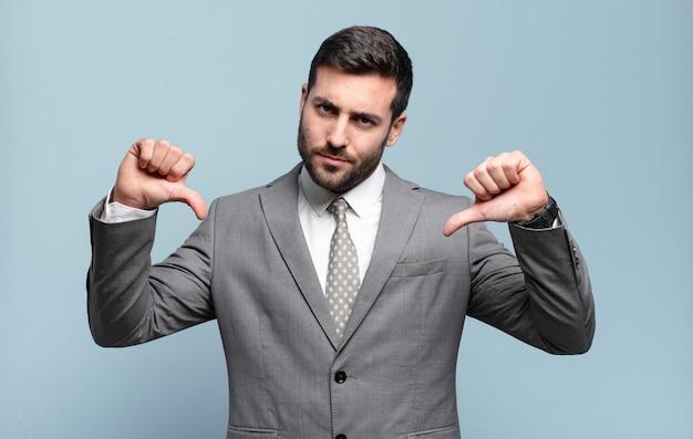 Jovem empresário bonito parecendo triste, desapontado ou zangado, mostrando os polegares para baixo em desacordo e sentindo-se frustrado