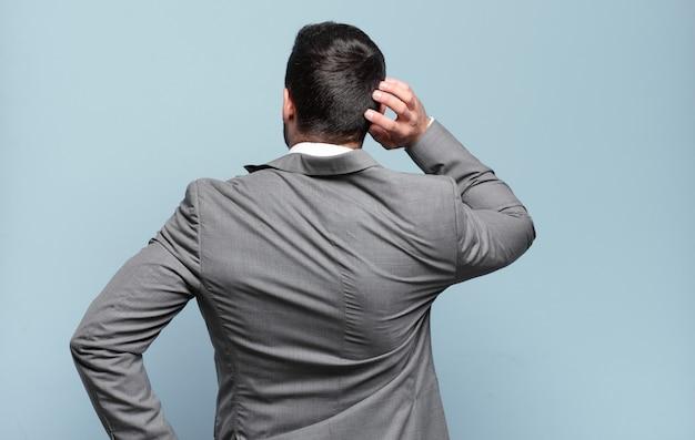 Jovem empresário bonito pensando ou duvidando, coçando a cabeça, sentindo-se perplexo e confuso, vista traseira ou traseira