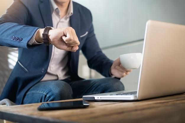 Jovem empresário bonito que trabalha no laptop com uma xícara de café no restaurante. e olhando para o relógio.