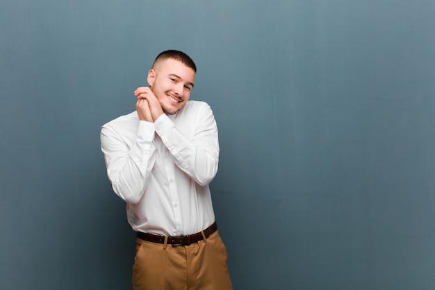 Jovem empresário bonito se apaixonando e parecendo fofo, adorável e feliz, sorrindo romanticamente com as mãos ao lado do rosto contra uma parede plana