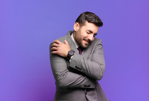 Jovem empresário bonito se sentindo apaixonado, sorrindo, acariciando e abraçando a si mesmo, permanecendo solteiro, sendo egoísta e egocêntrico