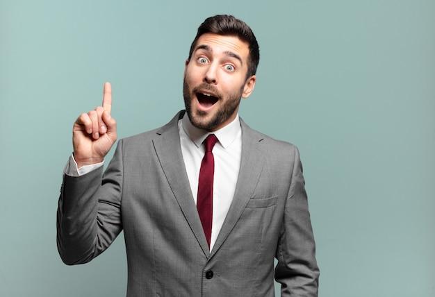 Jovem empresário bonito se sentindo como um gênio feliz e animado depois de realizar uma ideia, levantando o dedo alegremente, eureka!