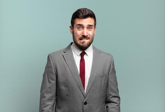 Jovem empresário bonito se sentindo sem noção, confuso e incerto sobre qual opção escolher, tentando resolver o problema