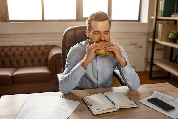 Jovem empresário bonito sentar à mesa e morder o hambúrguer em seu próprio escritório. ele tem hora do almoço. jovem com fome devora comida.