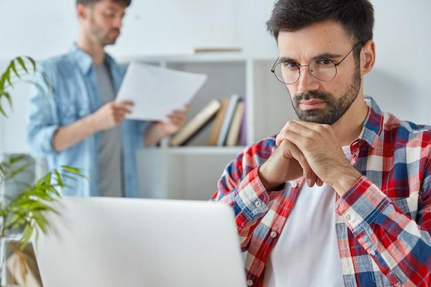 Jovem empresário bonito sério focado em laptop portátil, prepara projeto empresarial para reunião