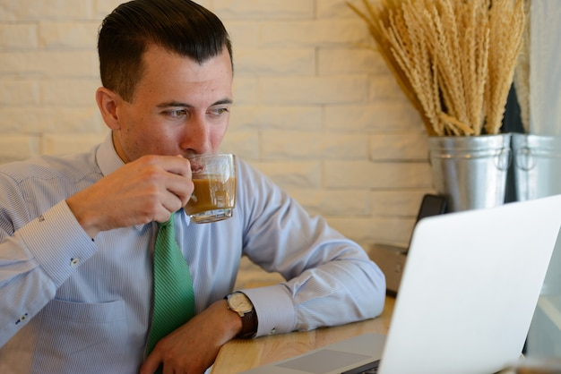 Jovem empresário bonito tomando café enquanto trabalhava em uma cafeteria