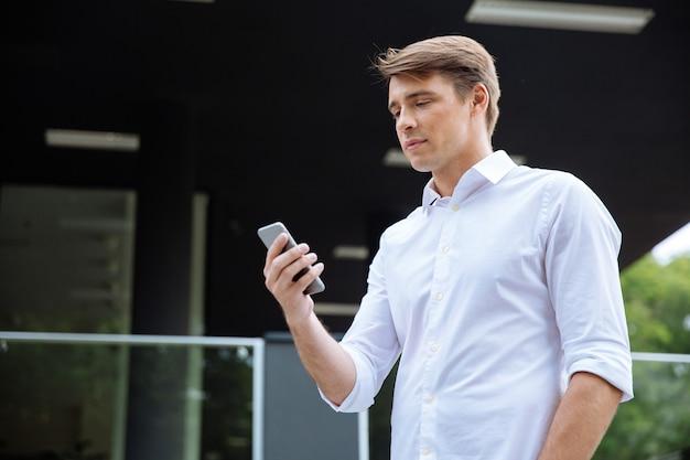 Jovem empresário bonito usando telefone celular ao ar livre