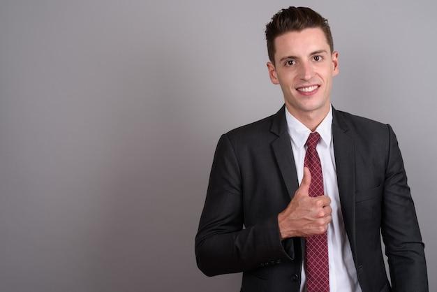 Jovem empresário bonito vestindo terno cinza