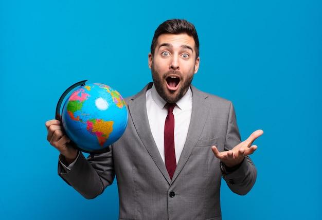 Jovem empresário boquiaberto e pasmo, chocado e atônito com uma surpresa inacreditável segurando um mapa do globo terrestre