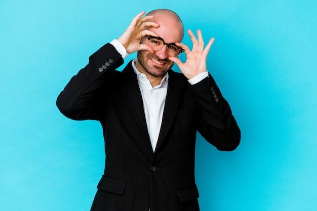 Jovem empresário, calvo, caucasiano, isolado na parede azul, mostrando sinais de aprovação sobre os olhos