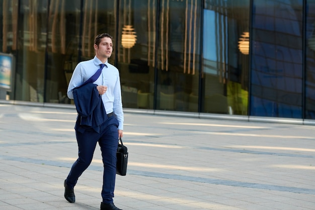 Jovem empresário cansado com caso indo atrás do trabalho em clima quente