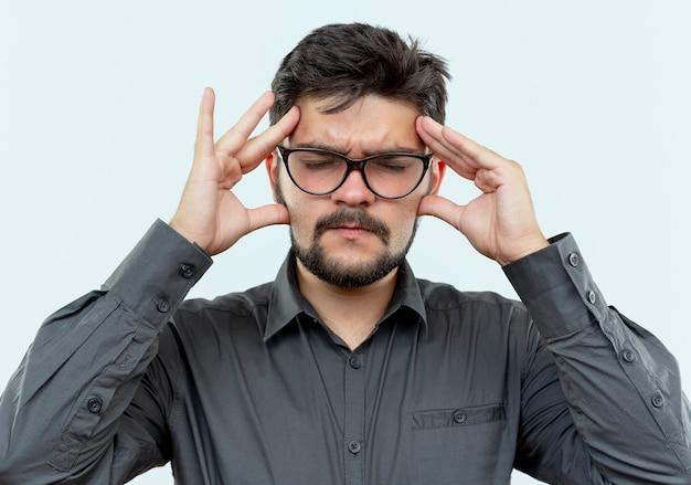 Jovem empresário cansado de óculos e colocando as mãos na testa isolado no branco