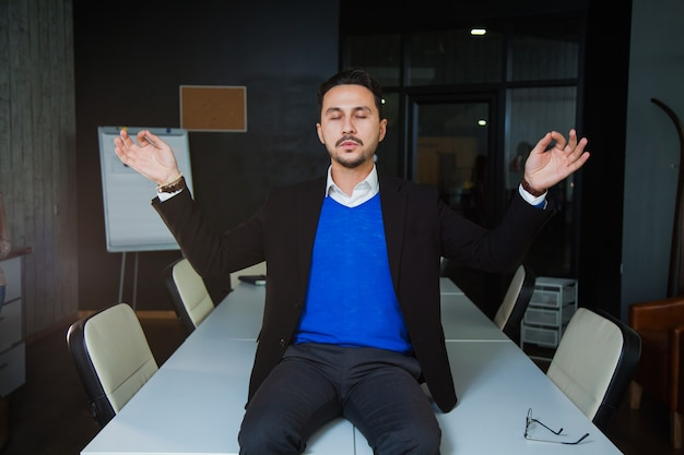 Jovem empresário cansado meditando na mesa em um escritório espaçoso