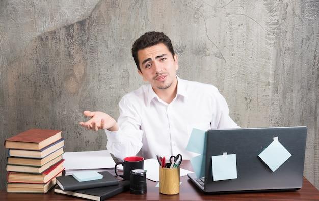 Jovem empresário, cansado, olhando para a câmera na mesa do escritório.