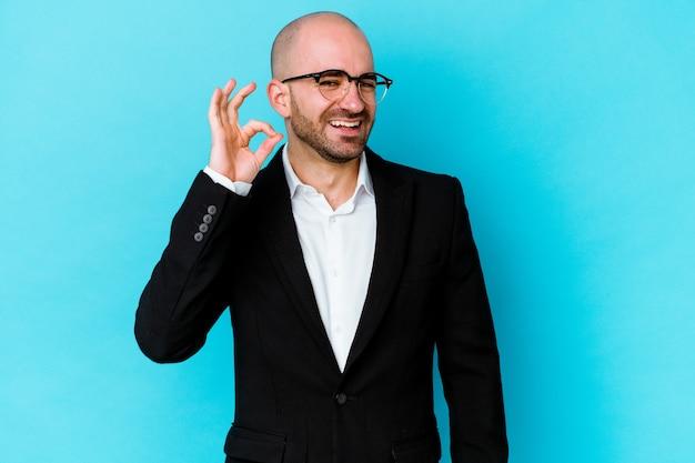 Jovem empresário careca, caucasiano, isolado na parede azul, pisca os olhos e faz um gesto de ok com a mão