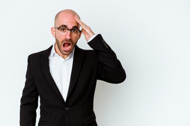Jovem empresário careca isolado na parede azul gritando alto, mantendo os olhos abertos e as mãos tensas
