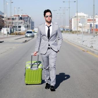 Jovem empresário carregando sua mala de viagem