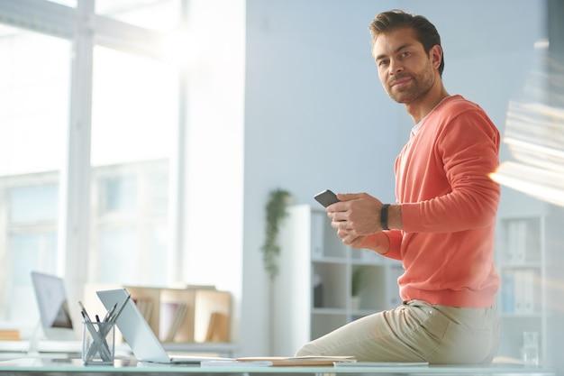 Jovem empresário casual com smartphone olhando para você enquanto está sentado na mesa do escritório