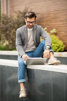 Jovem empresário casual sentado em um ambiente urbano enquanto assiste a um vídeo online no laptop