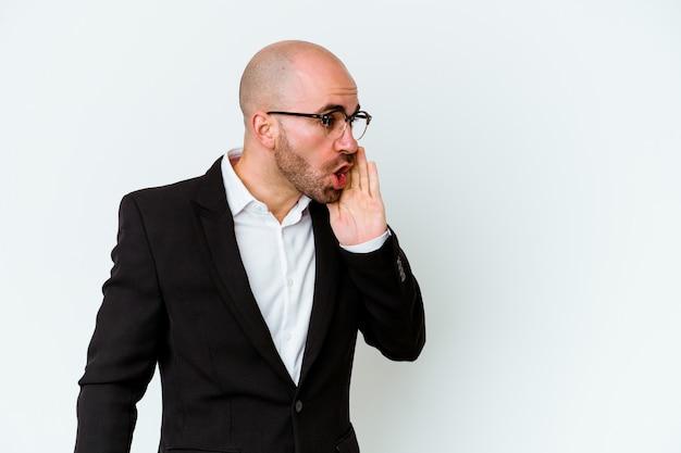 Jovem empresário, caucasiano, careca, isolado na parede azul, contando uma notícia secreta sobre a travagem e olhando para o lado